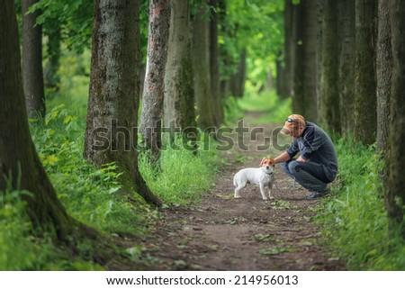 man and dog walking on park - stock photo