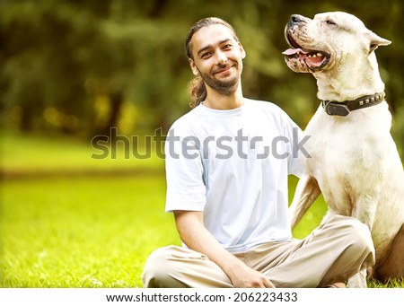 Man and Dogo Argentino walk in the park. - stock photo