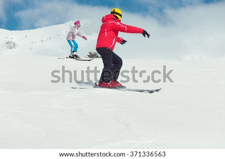 Man and girl go skiing on piste in high mountains - stock photo