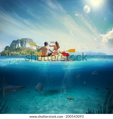 Man and girl kayaking next to a tropical island  - stock photo