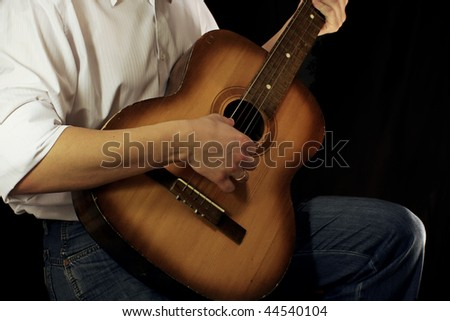 man and guitar at black background - stock photo