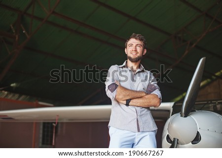 man and his airplane in hangar - stock photo
