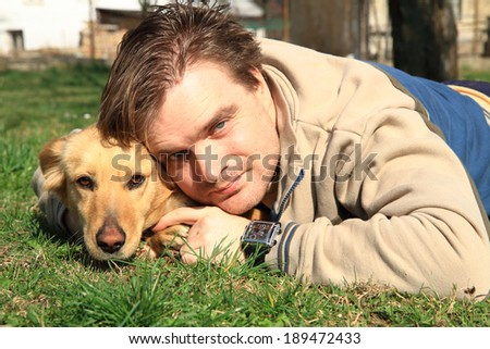 man and his dog in the grass - stock photo