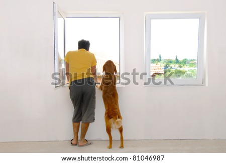 man and his dog looking through window back view - stock photo