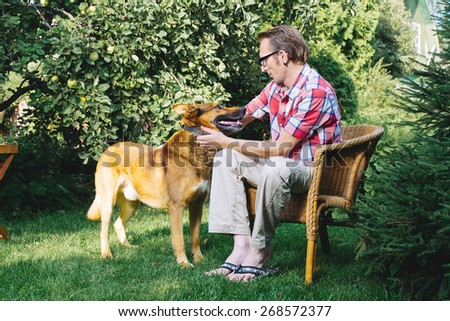 Man and his dog rest in the garden at summer day - stock photo