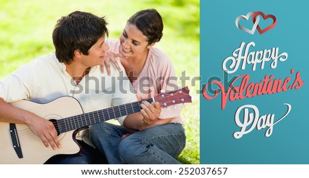 Man and his friend look at each other while he is playing the guitar against cute valentines message - stock photo