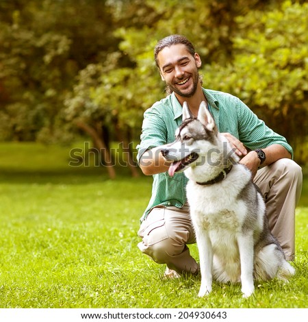 Man and Husky dog walk in the park. He keeps the dog on the leash. - stock photo