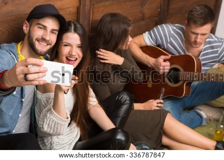 Man and lady friends making selfies while their friends playing the guitar and singing different songs. Happy people spending their weekends all together. - stock photo