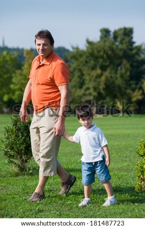 Man and little boy are walking in the park.  - stock photo