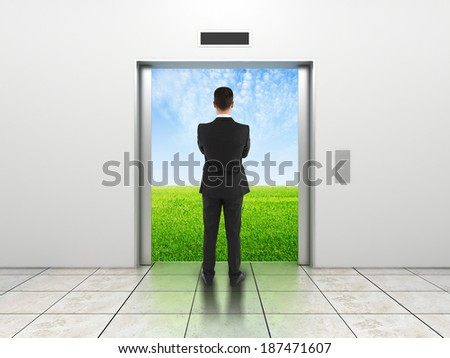 man and modern elevator with opened doors to field - stock photo