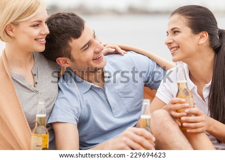 Man and two women relaxing on beach with beer. Happy friends drinking together on beach and smiling - stock photo