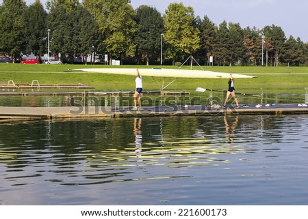 Man and woman, after rowing wear boat, on the lake shore  - stock photo