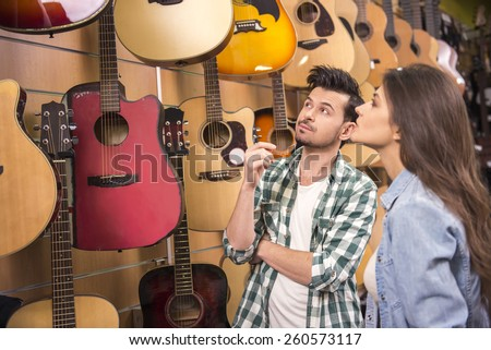 Man and woman are considering a guitars in a music store. - stock photo