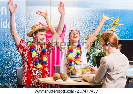 Man and woman booking vacation in travel agency cheering for a good deal - stock photo