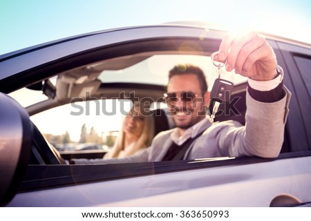 Man and woman bying a car.Men sitting in a car and showing car key. Focus on key. - stock photo