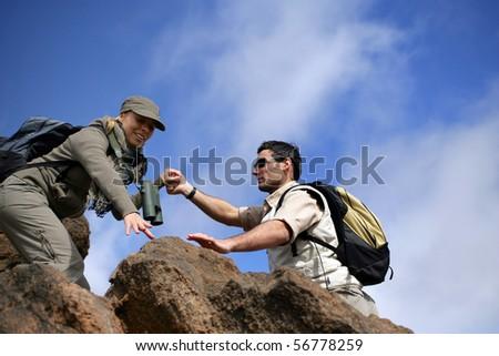 Man and woman climbing rocks - stock photo
