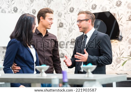 Man and woman consulting salesman for domestic kitchen in studio or furniture store - stock photo