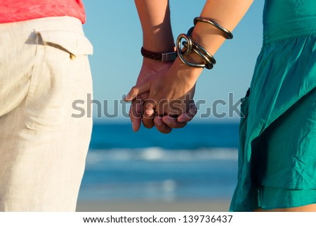 Man and woman, couple, enjoying the romantic sunset on a beach by the ocean in their vacation, they standing hand in hand, closeup - stock photo