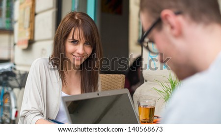 Man and woman couple in the cafe on laptop computer. They are happy. - stock photo