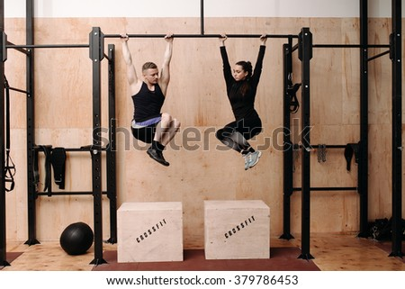 Man and woman doing exercise on horizontal bar - stock photo