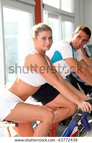 Man and woman doing indoor biking - stock photo