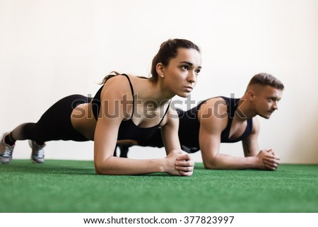 Man and woman doing plank exercises at the gym - stock photo