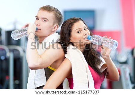 Man and woman drinking water after sport exercises. Fitness gym. - stock photo