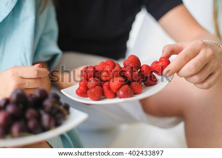 Man and woman eating Strawberry and cherry. Large, tasty strawberries on a white plate. Cherries on a plate blurred. Man holding a strawberry. Guy hugging girlfriend and gives her  strawberries. - stock photo