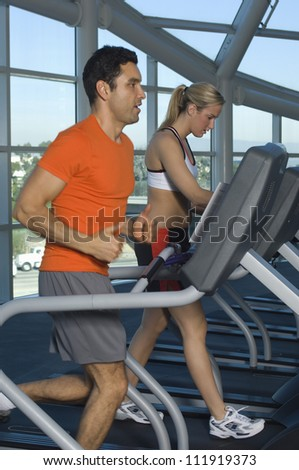 Man and woman exercising on treadmill - stock photo