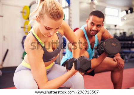 Man and woman exercising with dumbbells at a gym - stock photo