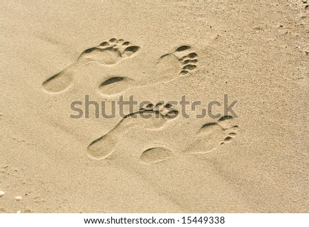 man and woman footprints on the beach - stock photo