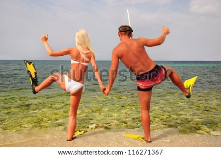 man and woman go to diving on summer beach - stock photo
