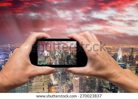 Man and woman hand capturing New York night lights with smartphone. - stock photo