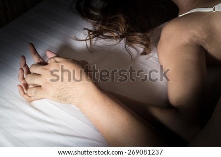 Man and woman hand in sex relationship on bed. - stock photo
