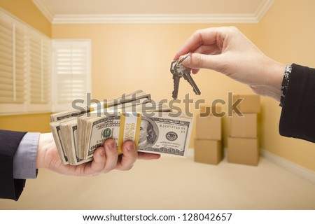 man and Woman Handing Over Cash For House Keys Inside Empty Room with Boxes. - stock photo