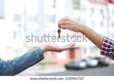 Man and woman hands hold keys near apartment house - stock photo