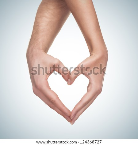 man and woman hands show heart gesture isolated on blue gradient background - stock photo