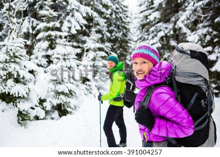 Man and woman happy couple hikers trekking in white winter woods and mountains. Young people walking on snowy trail with backpacks, healthy lifestyle adventure, camping on hiking trip, Poland. - stock photo