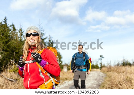 Man and woman hikers hiking on mountain trail autumn or winter nature. Young couple backpackers walking in forest landscape. Happy trekkers on travel trip with backpacks, camping outdoors. - stock photo