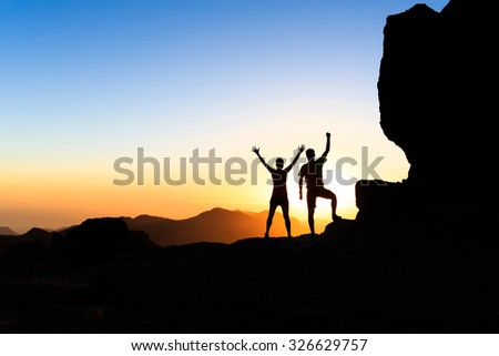 Man and woman hikers trekking in summer mountains, accomplish arms outstretched. Young couple on rocky mountain range looking at beautiful inspirational landscape view, Gran Canaria Canary Islands. - stock photo