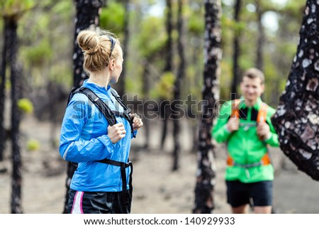 Man and woman hikers trekking on volcanic trail in mountains. Young couple hiking on La Palma, Canary Islands. Sport and exercising in summer nature outdoors. - stock photo