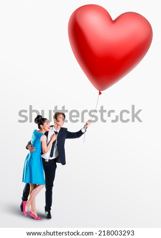 Man and woman holding a heart- shaped balloon - stock photo