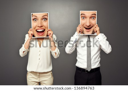 man and woman holding amazed happy faces. concept photo over grey background - stock photo