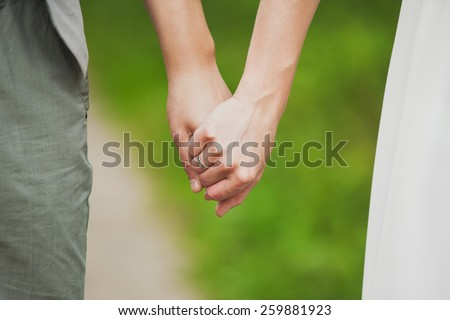 man and woman holding hands. young couple in love standing together. bride and groom. family - stock photo