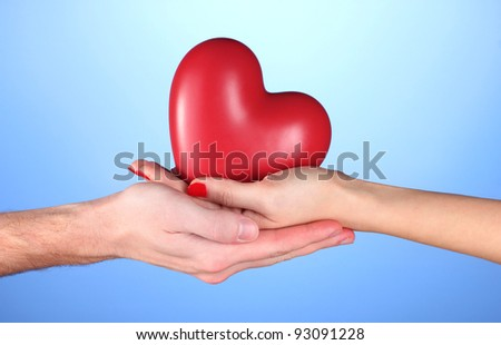 Man and woman holding red heart in hands on blue background - stock photo