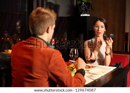 man and woman in a restaurant. woman is making up - stock photo