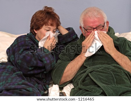Man and woman in bed blowing noses - stock photo