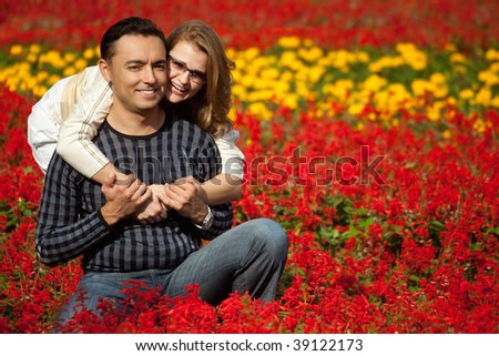 man and woman in brackets laughing in the flowers - stock photo