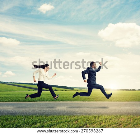 man and woman in formal wear running fast on the road at outdoor against the background of beautiful scenery - stock photo