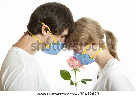 Man and woman   in  respirators smelling rose  against white background - stock photo